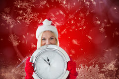 Composite image of happy festive blonde with clock Stock Images