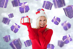 Composite image of happy festive blonde with gift Stock Image