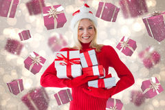 Composite image of happy festive blonde with gift Royalty Free Stock Images