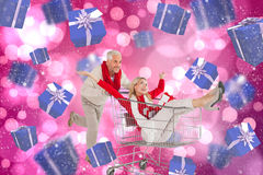 Composite image of happy festive couple messing in trolley Stock Photo