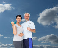 Composite image of happy fit couple with dumbbell and water bottle Royalty Free Stock Photo