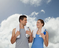 Composite image of happy fit young couple with water bottles Royalty Free Stock Photos