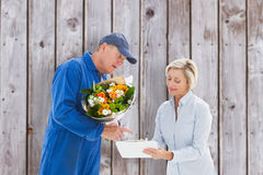 Composite image of happy flower delivery man with customer. Happy flower delivery men with customer against wooden planks royalty free stock images