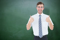 Composite image of happy geeky businessman with thumbs up Royalty Free Stock Photography