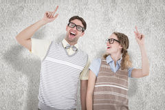 A Composite image of happy geeky hipster couple pointing up Stock Photos