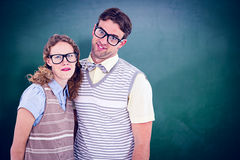 Composite image of happy geeky hipster couple with silly faces Stock Image