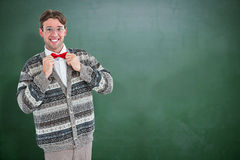 Composite image of happy geeky hipster with wool jacket. Happy geeky hipster with wool jacket against green chalkboard stock image
