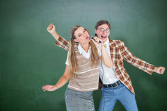 Composite image of happy geeky hipsters singing with microphone Stock Image