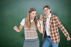 Composite image of happy geeky hipsters singing with microphone Stock Photos