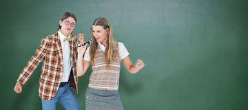 Composite image of happy geeky hipsters singing with microphone Royalty Free Stock Photography