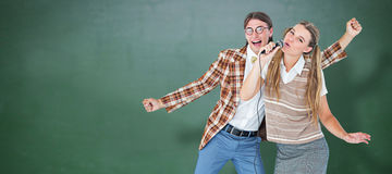 Composite image of happy geeky hipsters singing with microphone Stock Photography