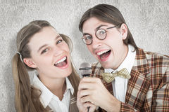 A Composite image of happy geeky hipsters singing with microphone Stock Image