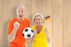 Composite image of happy german couple cheering at camera holding ball Royalty Free Stock Photography