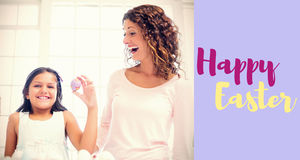 Composite image of happy girl holding easter egg stock photo