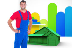 Composite image of happy handyman in overalls with hands on hip Royalty Free Stock Images