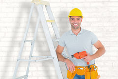 Composite image of happy handyman with power drill leaning on ladder. Happy handyman with power drill leaning on ladder against white wall Royalty Free Stock Image