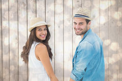 Composite image of happy hipster couple holding hands and smiling at camera Stock Photo