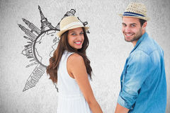 Composite image of happy hipster couple holding hands and smiling at camera Stock Image
