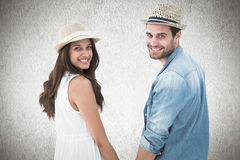 Composite image of happy hipster couple holding hands and smiling at camera Stock Images