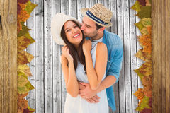 Composite image of happy hipster couple hugging and smiling Stock Photos