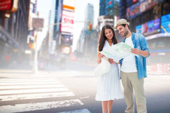 Composite image of happy hipster couple looking at map. Happy hipster couple looking at map against blurry new york street Royalty Free Stock Photos