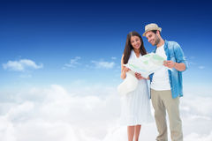 Composite image of happy hipster couple looking at map. Happy hipster couple looking at map against bright blue sky over clouds Royalty Free Stock Image