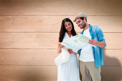 Composite image of happy hipster couple looking at map Royalty Free Stock Images