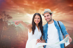 Composite image of happy hipster couple looking at map Royalty Free Stock Photography