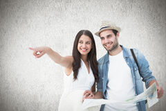 Composite image of happy hipster couple looking at map Royalty Free Stock Photo