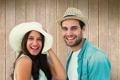 Composite image of happy hipster couple smiling at camera Stock Photo