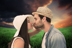 Composite image of happy hipster couple about to kiss Stock Photo