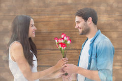 Composite image of happy hipster giving his girlfriend roses Stock Photo