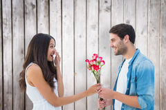 Composite image of happy hipster giving his girlfriend roses. Happy hipster giving his girlfriend roses against wooden planks stock photos