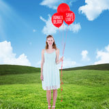 Composite image of happy hipster woman holding balloons. Happy hipster woman holding balloons against blue sky over green field Stock Image