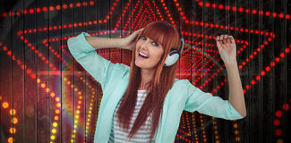 Composite image of happy hipster woman listening music with headphone Stock Images