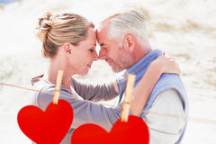 Composite image of happy hugging couple on the beach looking at each other. Happy hugging couple on the beach looking at each other against hearts hanging on a Stock Photo