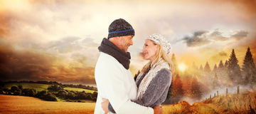 Composite image of happy husband holding wife while looking at each other Stock Photos