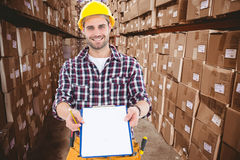Composite image of happy male repairman showing clipboard Stock Photography