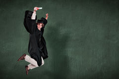 Composite image of happy male student in graduate robe jumping Royalty Free Stock Photo