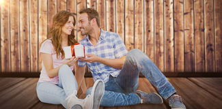 Composite image of happy man giving gift to woman Royalty Free Stock Photo