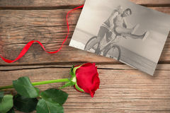 Composite image of happy man giving girlfriend a lift on his crossbar Stock Images