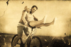 Composite image of happy man giving girlfriend a lift on his crossbar Stock Photography