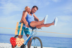 Composite image of happy man giving girlfriend a lift on his crossbar Royalty Free Stock Photography