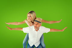 Composite image of happy man giving his partner a piggy back Royalty Free Stock Photos