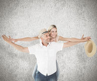 Composite image of happy man giving his partner a piggy back Stock Photo
