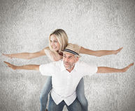 Composite image of happy man giving his partner a piggy back Stock Image