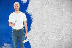 Composite image of happy man holding paint roller and paintbrush Royalty Free Stock Photo