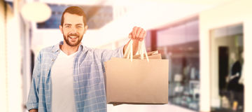 Composite image of happy man holding shopping bag Royalty Free Stock Photo