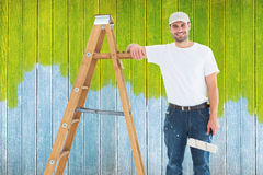 Composite image of happy man with paint roller standing by ladder Royalty Free Stock Photo