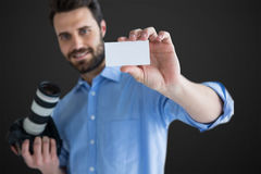 Composite image of happy man showing identity card while holding camera. Happy man showing identity card while holding camera against grey vignette Royalty Free Stock Photography